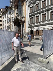 Mann mit Langstock am Blindenleitsystem auf der Straße